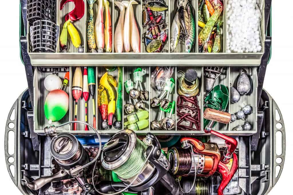 tackle box filled with lures and other fishing gear and reels spinning