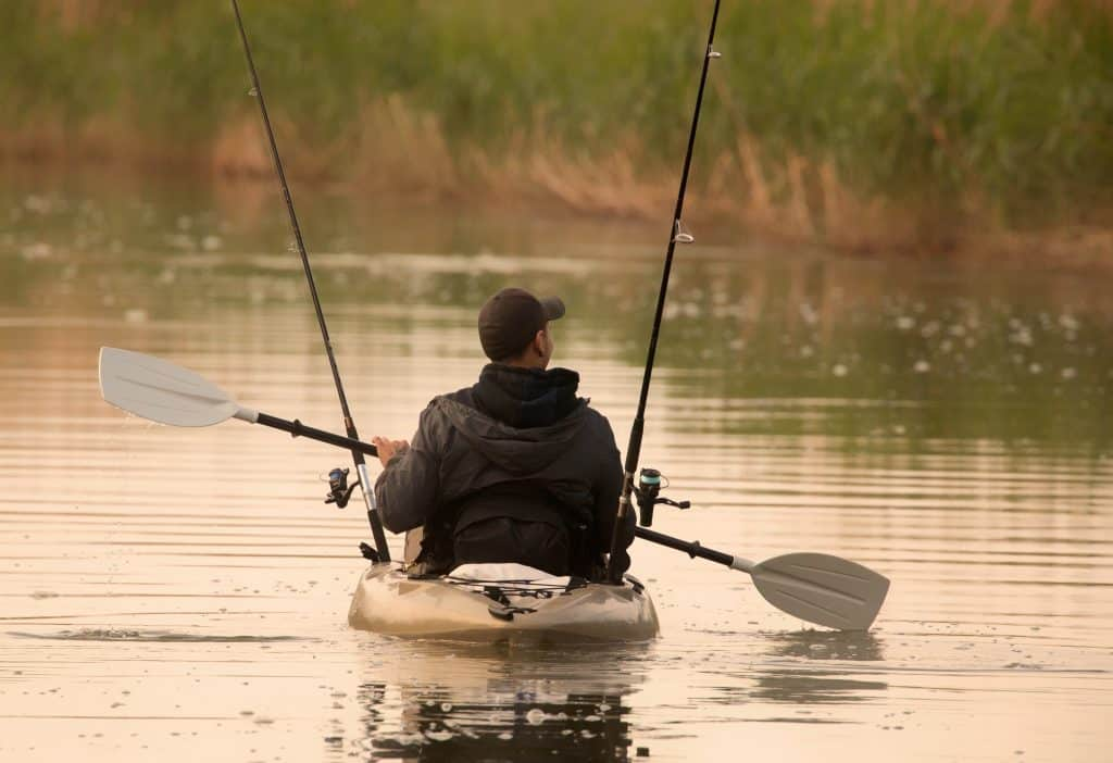 kayak fishing guy paddling on lake with fishing rods excellent