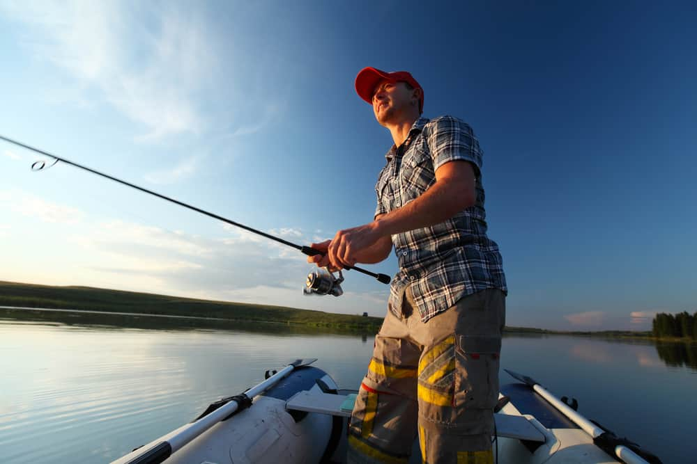 feature image for my article on summer bass fishing of a fisherman casting from a boat in the sunshine