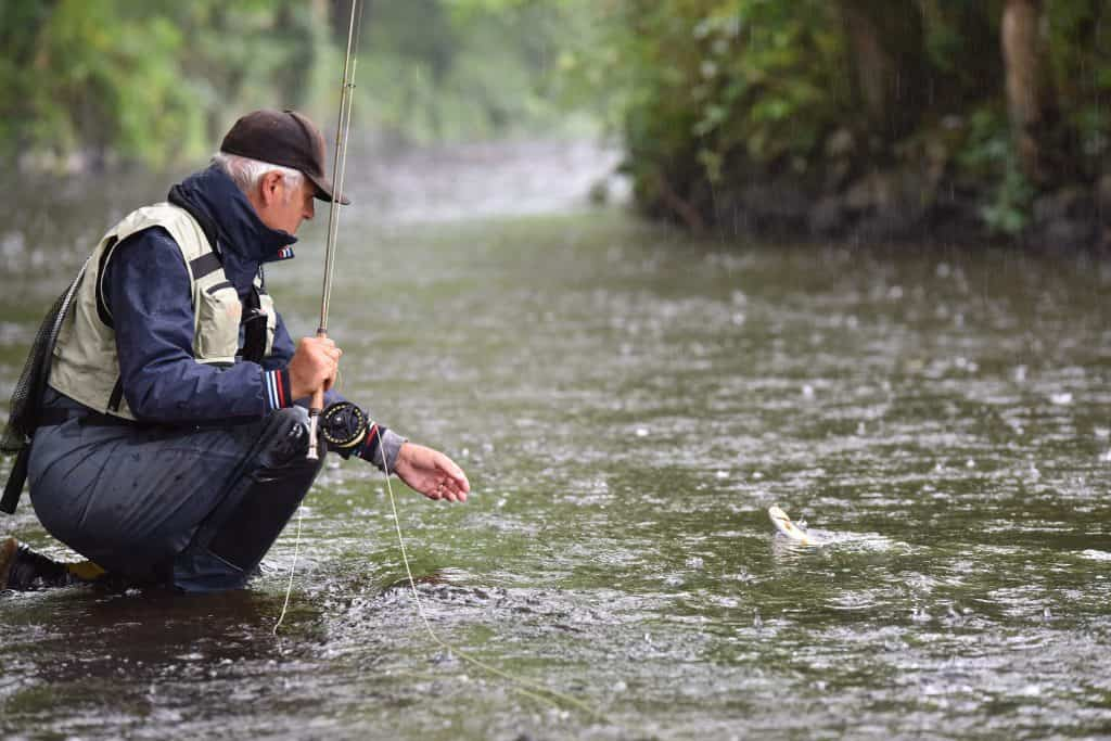 Fly fisherman catching trout in river under the rain