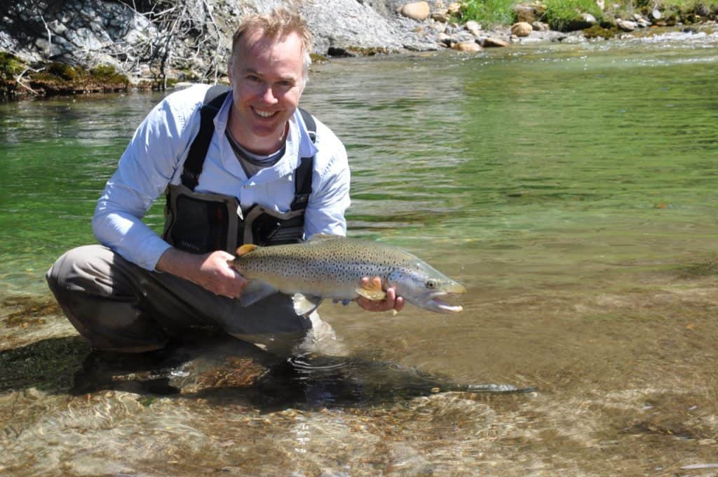 Fisherman holds big brown trout in New Zealand stream Rick Wallace