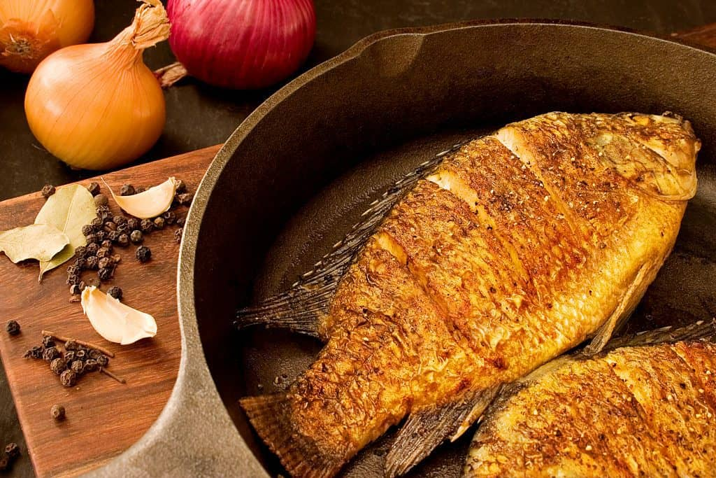 Can You Eat Bass? image of a bass being fried in a fry pan to illustrate the possibilities of cooking this fish