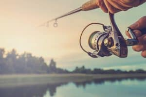 Sun picture of a man holding a spinning reel and rod winding handle
