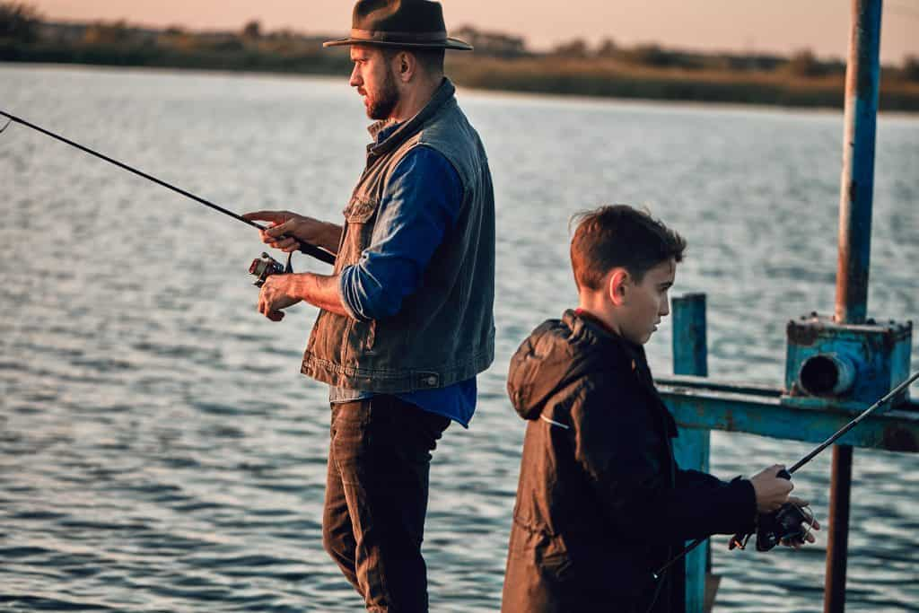 family father son fishing pier spinning reels and rods