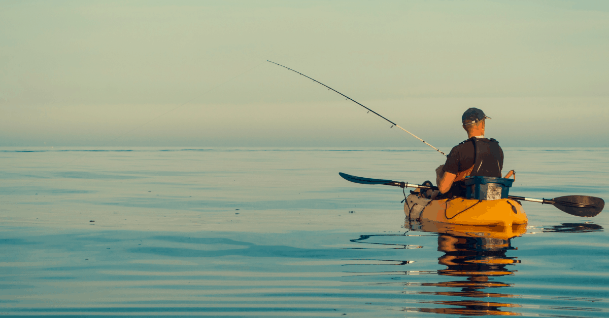 Excellent picture of a man fishing in a kayak in calm ocean