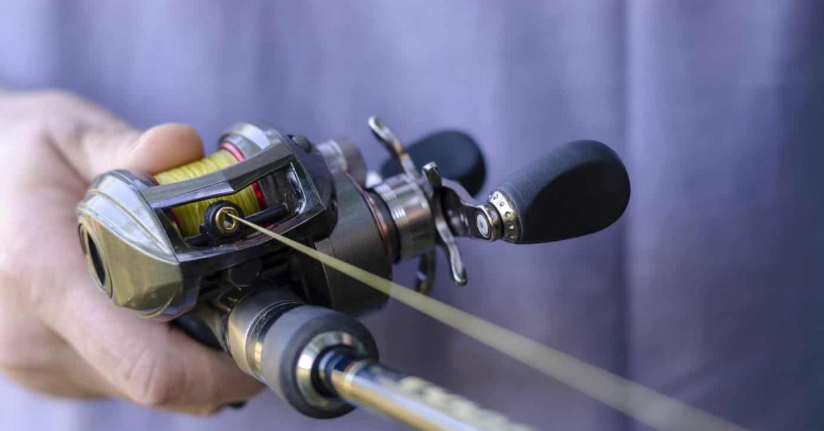 Close-up of male hand with a fishing rod and  baitcasting reel. Caucasian man is fishing with casting rod. Sports and recreation. Selective focus.