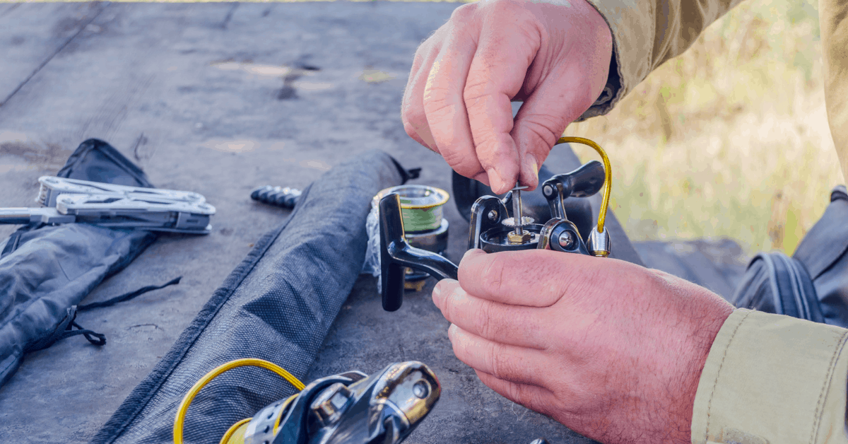 Picture of a man fixing a fishing reel holding the reel in his hands with some tools and parts